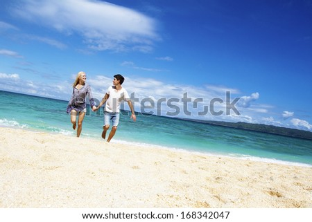 young happy loving couple on beach and sea background