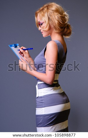 young happy sexy businesswoman in blue dress makes some notes in notepad