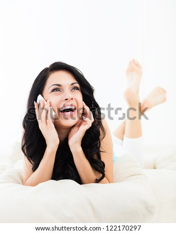 Young happy smile woman phone call on sofa in living room, at home - indoors, excited girl lying talking cellphone