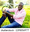 Young happy smiling african american wearing pink shirt with bicycle behind him in a park - stock photo