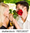 Young happy smiling cheerful attractive couple celebrating with glasses of champagne and rose, outdoors - stock photo