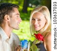 Young happy smiling cheerful couple with gifts, rosa and champagne, outdoor - stock photo