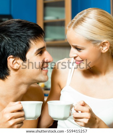 Young happy smiling couple drinking coffee together at home. Love, relations, romantic concept shoot.