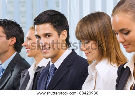 Young happy smiling successful businesspeople at meeting, presentation or conference. Focus on man looking at camera.