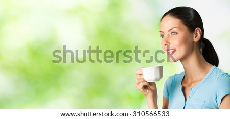 Young happy smiling woman drinking coffee, outdoors. To provide maximum quality, I have made this image, by combination of two photos.