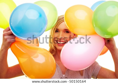 Young happy woman holding many colorful balloons