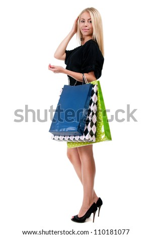 Young happy woman in black dress with colorful shopping bags on a white background