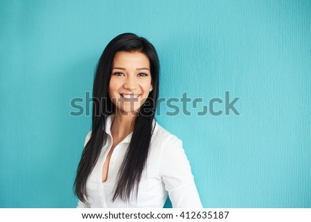 Young happy woman leaning against a blue wall