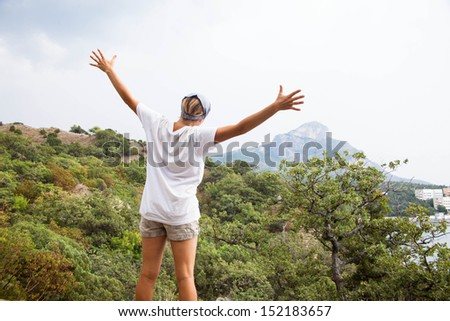 Young happy woman  standing on a rock