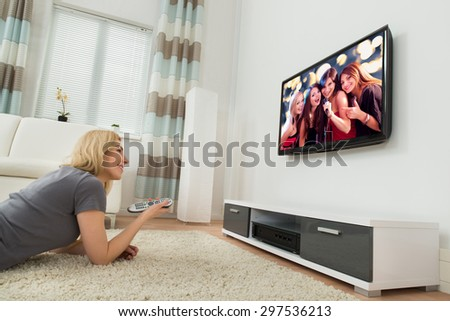 Young Happy Woman Watching Television While Lying On Carpet At Home