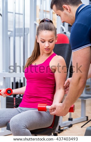 Young, healthy, attractive adult girl performing biceps muscle workout with professional, personal instructor / trainer at the gym on a bench.