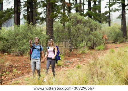 Young hiker couple hiking and pointing in the nature