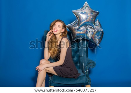 young hipster beautiful woman, evening dress, trend fashion style, blue background, sitting in chair, silver balloons, smiling, happy, celebrating birthday