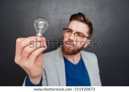 Young hipster with bulb in studio. looking at bulb. close up cool portrait. isolated black background