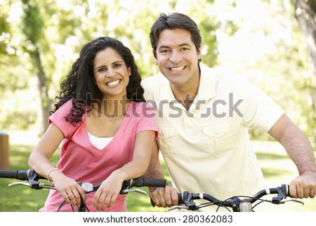 Young Hispanic Couple Cycling In Park
