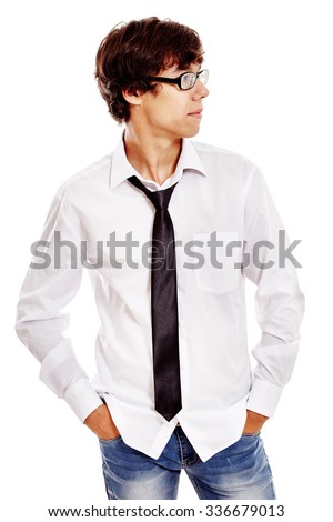 Young hispanic man wearing white shirt, blue jeans, black tie and glasses standing with hands in his pockets and looking aside isolated on white background