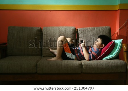 Young kid using a tablet or smartphone on a couch Photo of a Young kid using a tablet or smartphone on a couch