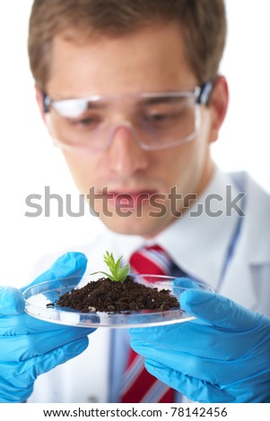 young lab assistant holds small flat dish with soil and plant, wears blue protective gloves, isolated on white