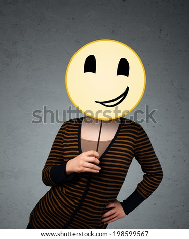 Young lady holding a yellow happy face emoticon in front of her head