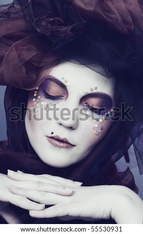 Young lady in original hat with creative make-up in doll-style.