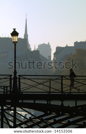 Young lady jogging in the heart of Paris on the footbridge Pont des Arts. Notre-Dame cathedral in the background.