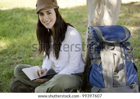 Young latin brunette writing on a journal about her hiking trip