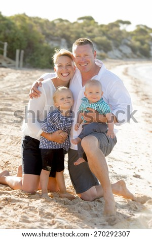 young lovely and beautiful wife and husband holding little daughter and baby boy posing on beach sand sea shore smiling happy in family love and Summer vacation concept