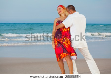 Young loving couple have a fun on the beach
