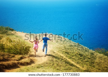 Young loving couple jumping and having fun on the beach, enjoying their summer holiday together. Honeymoon.