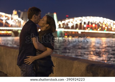 Young loving couple kissing on granite embankment against Bolsheokhtinsky bridge in St. Petersburg, Russia. White nights