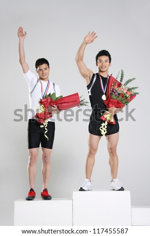 Young male athletes holding trophy and flowers