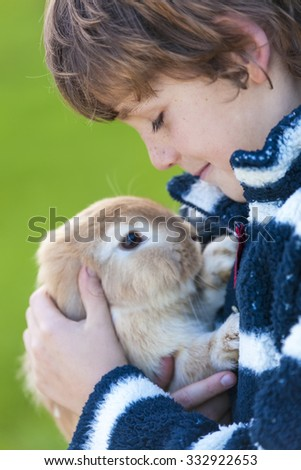Young male boy child outside playing with his pet rabbit