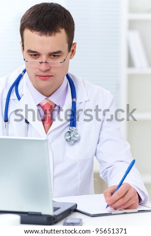 young male doctor working at a table with a laptop
