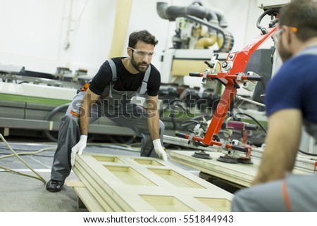 Young male workers work in a factory for the production of furniture
