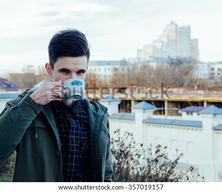 Young man and cup with coffee on the autumn city street
