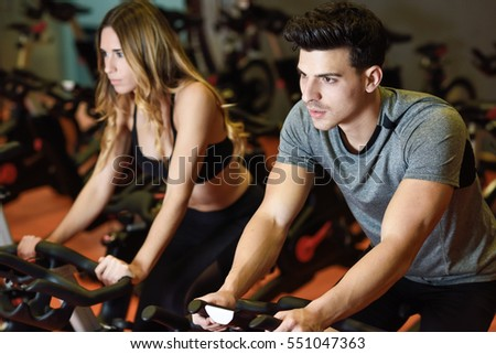 Young man and woman biking in the gym, exercising legs doing cardio workout cycling bikes. Two people in a spinning class wearing sportswear.