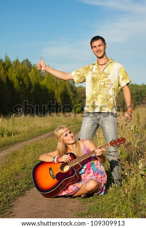 young man and woman with guitar. hippie hitch-hike