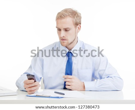 young man at office reading text message on mobile phone