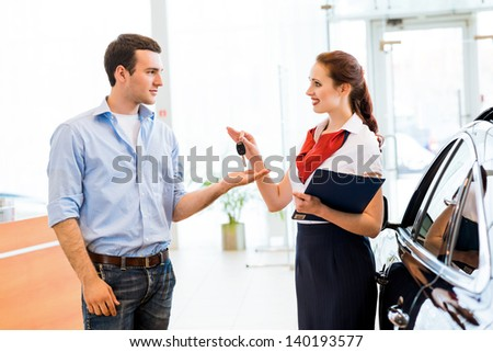young man bought the car and takes the consultant keys from the new car