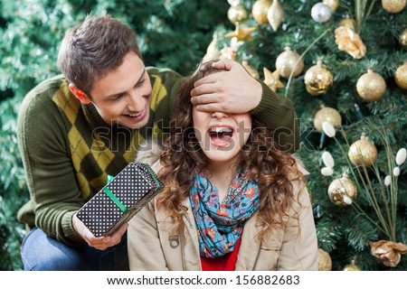 Young man covering woman's eyes while surprising her with gift in Christmas store