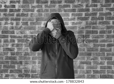 Young man covers his eyes and mouth with hands ,black and white