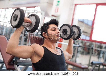 Young man exercising with dumbbells in a gym.