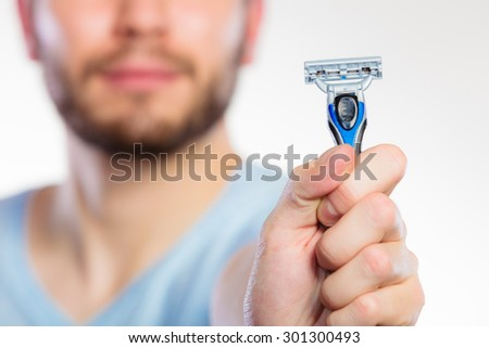 Young man guy with beard showing disposable blue razor blade, studio shot on white background. Cropped image