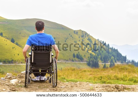 Young man in a wheelchair enjoying fresh air in a sunny day on the mountain