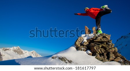 Young man in a yoga pose in winter mountains