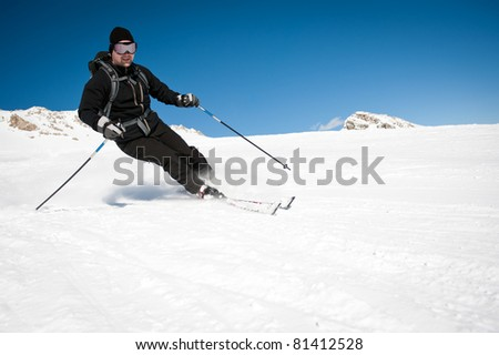 young man in black clothing skiing on mountain slope