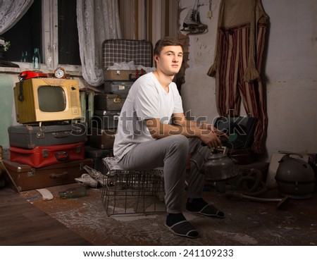 Young Man in Casual Outfit Sitting at the Junk Room Looking at Camera.