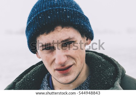 Young man in hat sataying on the winter field