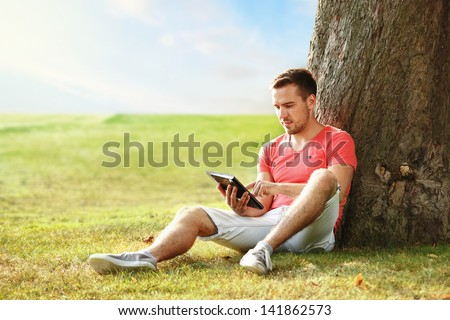young man in pink t-shirt with tablet in the park