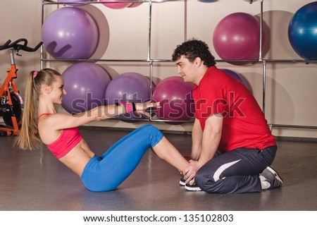 young man instructs woman in the fitness club